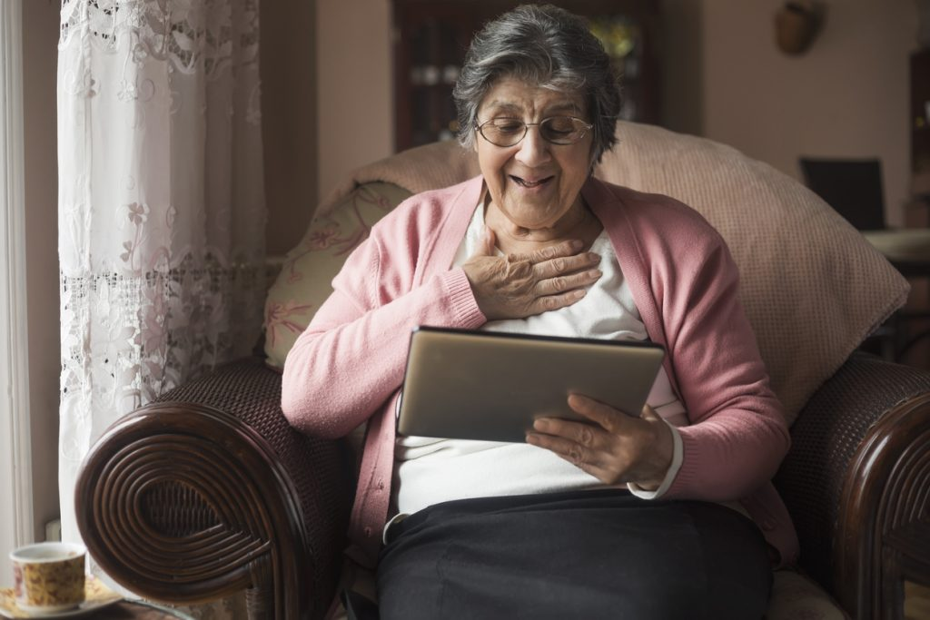Senior woman sat in armchair with one hand on chest as she looks at tablet computer